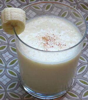 Een glas ananas smoothie met een stukje banaan op de rand en wat nootmuskaat  over het smoothie gestrooid