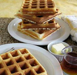 Stapeltje gebakken Brusselse wafels met boter en honing geserveerd