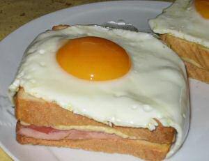 Croque madame met hesp en kaas onder een gebakken omelet
