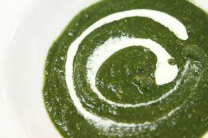 Een bord groene spinaziesoep met room
