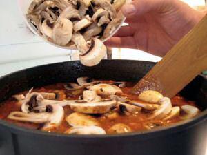 Een pot Vlaams varkensstoofvlees met verse champignons