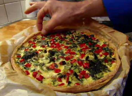 Lekkere vegetarische groentenquiche met paprika's, ui, champignons, spinazie in een beslag van room, eieren en kruidenkaas